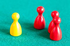 One yellow pawn in front of three red pawns stock photos