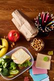 Concept of school lunch break with healthy lunch box and school supplies on wooden desk, selective focus. Concept of school lunch break with healthy lunch box Royalty Free Stock Photos