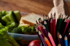 Concept of school lunch break with healthy lunch box and school supplies on wooden desk, selective focus. Concept of school lunch break with healthy lunch box Royalty Free Stock Images