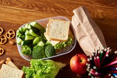 Concept of school lunch break with healthy lunch box and school supplies on wooden desk, selective focus. Concept of school lunch break with healthy lunch box Stock Image