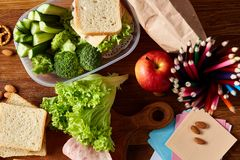 Concept of school lunch break with healthy lunch box and school supplies on wooden desk, selective focus. Concept of school lunch break with healthy lunch box Royalty Free Stock Photography