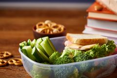 Concept of school lunch break with healthy lunch box and school supplies on wooden desk, selective focus. Concept of school lunch break with healthy lunch box Royalty Free Stock Image