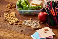 Concept of school lunch break with healthy lunch box and school supplies on wooden desk, selective focus. Concept of school lunch break with healthy lunch box Stock Photo