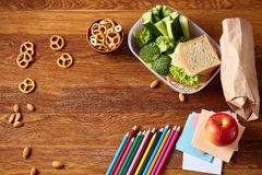 Concept of school lunch break with healthy lunch box and school supplies on wooden desk, selective focus. Concept of school lunch break with healthy lunch box Stock Images