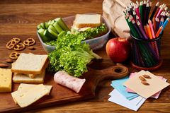 Concept of school lunch break with healthy lunch box and school supplies on wooden desk, selective focus. Concept of school lunch break with healthy lunch box Royalty Free Stock Photo