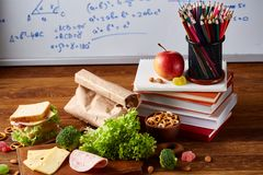 Concept of school lunch break with healthy lunch box and school supplies on wooden desk, selective focus. Concept of school lunch break with healthy lunch box Stock Photography