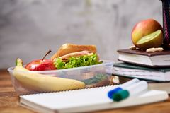 Concept of school lunch break with healthy lunch box and school supplies on wooden desk, selective focus.
