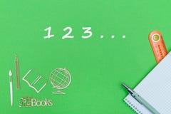 Numbers 123, school supplies wooden miniatures, notebook on green background. Concept school, numbers 123, school supplies, notebook, ruler and pen on green Stock Image