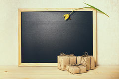 Concept of school is over, happy holidays, blank school new black board with tulip and gift boxes, close up royalty free stock images