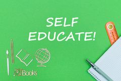 Text self educate, school supplies wooden miniatures, notebook on green background. Concept school, text self educate, school supplies, notebook, ruler and pen stock photography