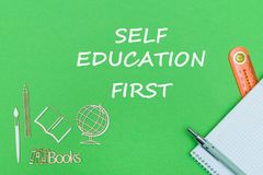 Text self education first, school supplies wooden miniatures, notebook on green background. Concept school, text self education first, school supplies, notebook Royalty Free Stock Image