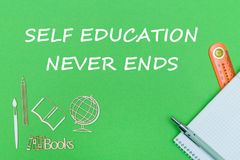 Text self education never ends, school supplies wooden miniatures, notebook on green background. Concept school, text self education never ends, school supplies Royalty Free Stock Image