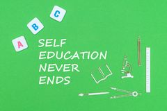 Text self education never ends, from above wooden minitures school supplies and abc letters on green background. Concept school, text self education never ends Royalty Free Stock Photo