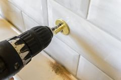 Concept of the screwdriver, screw tightening and mounting fasteners for the soap holder. The concept of the screwdriver, screw tightening and mounting fasteners stock images