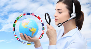 Concept search, woman with headset, globe, flags and magnifying Royalty Free Stock Photos