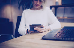 Concept of searching for new business project.Pensive young beautiful businesswoman using tablet while sitting at her Stock Photos