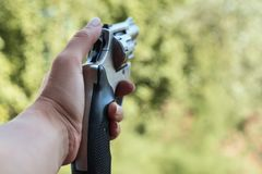 The concept of security. The gun in the hand of a woman. The girl is preparing to shoot stock image