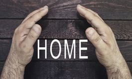Concept security of property, home insurance. Insurance agent`s hands protectubg home text on wood.  Stock Photo