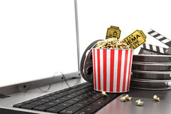 Concept of see online film. Film reels, clapperboard and pop corn on laptop keyboard Stock Image