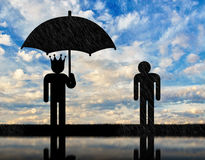 Concept of selfishness and greed. Man with a crown under an umbrella and a man in rain Royalty Free Stock Image