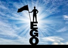 Concept of selfishness and narcissism. Silhouette of a selfish man who holds a flag on top of the word ego. The concept of selfishness and narcissism Royalty Free Stock Photos