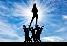 Concept of selfishness and narcissistic personality. Silhouette of a selfish and narcissistic woman with a crown on her head standing on the hands of men. The Stock Image