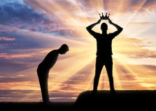 Concept of selfishness and narcissistic. Silhouette of a man dresses his crown, and a servant bows to him Royalty Free Stock Photography