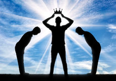 Concept of selfishness and narcissistic. Silhouette of a selfish man dresses his crown, and servants bow to him Royalty Free Stock Images