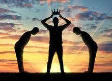 Concept of selfishness and narcissistic. Silhouette of a selfish man dresses his crown, and servants bow to him Stock Image