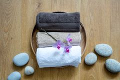 Concept of sensuality, clean softness or chic bodycare, top view. Pampering towels and zen stones on round wooden background for concept of pure sensuality Stock Photo