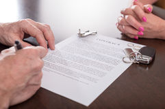 Concept of separation of a couple. Husband signing separation contract infront of his wife (random english dummy text used Royalty Free Stock Photography
