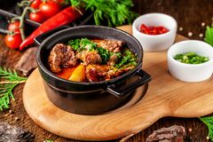 The concept of Serbian cuisine. Juicy baked beef in its own juice with potatoes, vegetables and greens. Serve in an iron fire. On a wooden board royalty free stock photography