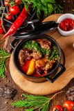 The concept of Serbian cuisine. Juicy baked beef in its own juice with potatoes, vegetables and greens. Serve in an iron fire. On a wooden board stock photo