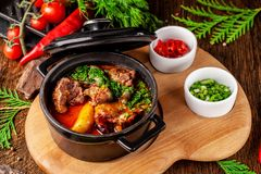 The concept of Serbian cuisine. Juicy baked beef in its own juice with potatoes, vegetables and greens. Serve in an iron fire. On a wooden board stock photos