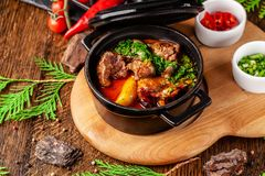 The concept of Serbian cuisine. Juicy baked beef in its own juice with potatoes, vegetables and greens. Serve in an iron fire. On a wooden board stock photography