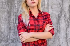 Concept of serious, confident and hard-working worker or student. Thoughtful young woman with blonde hair, dressed in red checkere royalty free stock images