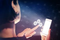 Concept of setting and support service. Image of a girl with a smartphone in hands. She presses on the gears icon. Concept of setting and support service Stock Photo