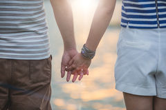 Concept shoot of friendship and love of man and woman: two hands. Over sun ray and nature Stock Photo