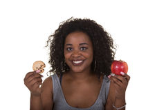 Concept shoot about health care of a woman choosing between an apple and a cookie Stock Image