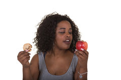 Concept shoot about health care of a woman choosing between an apple and a cookie Royalty Free Stock Photo