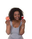 Concept shoot about health care of a woman choosing between an apple and a pill bottle Royalty Free Stock Photos