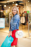 Concept Shopping. Portrait of beauty blonde smiling woman in casual holding shopping bags near shop in the shopping Royalty Free Stock Photos