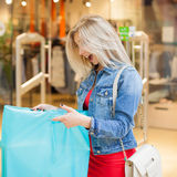 Concept Shopping. Portrait of beauty blonde woman in casual clothes surprising purchases near shop in the shopping Royalty Free Stock Image