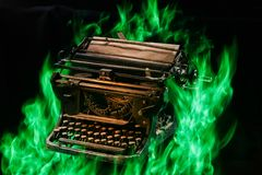 Concept shot of antique manual typewriter with paper burning on black background, selective focus stock images