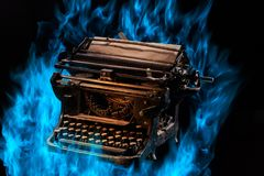 Concept shot of antique manual typewriter with paper burning on black background, selective focus. Concept picture of antique manual typewriter with paper Royalty Free Stock Image