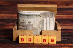 Bribe. Concept shot of bribe on wooden background stock photo