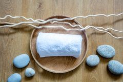 Concept of shower, hygiene with pure white towel and twigs. Concept of shower, hygiene and purity with white rolled up towel on wooden tray over natural twigs Stock Photo