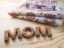 Word Mom biscuit over the wood background. The concept of a single parent. Stock Photo