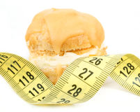 Concept of slimming, caramel cake with measuring tape Stock Photography