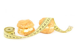 Concept of slimming, caramel cakes with measuring tape Stock Photo